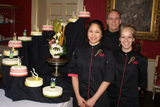 Lotte Bode, Marlon Koning en Lotte Dierick poseren trots naast de taart.  Foto: NBOV