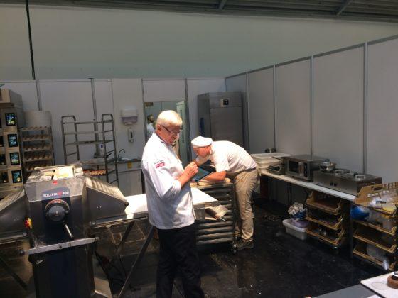 Juryvoorzitter Günther Koerffer inspecteert de Nederlandse wedstrijdbox waar Heiloo en Schröder aan het werk zijn.