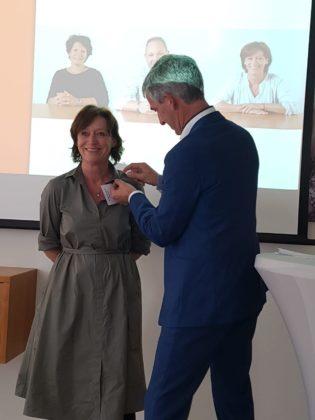Voorzitter Jos den Otter speldt Mariëlle van Heeswijk de gouden NBOV-broche op.