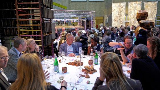 Op de achtergrond het werk Van Bloem naar Brood van kunstenaar/uitvinder Ap Verheggen. Pater hoopt uit de tarwehalmen tenminste graan voor één broodje te kunnen halen.